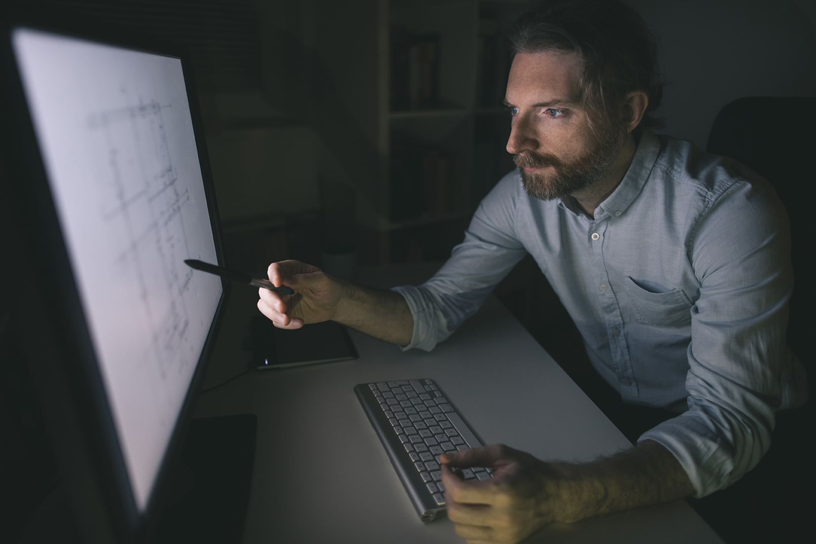 Bearded man working on computer from his home office.Construction engineer checks his construction project.